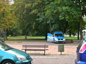 Police officers on watch beside the Alberto Adriano memorial in Stadtpark Dessau